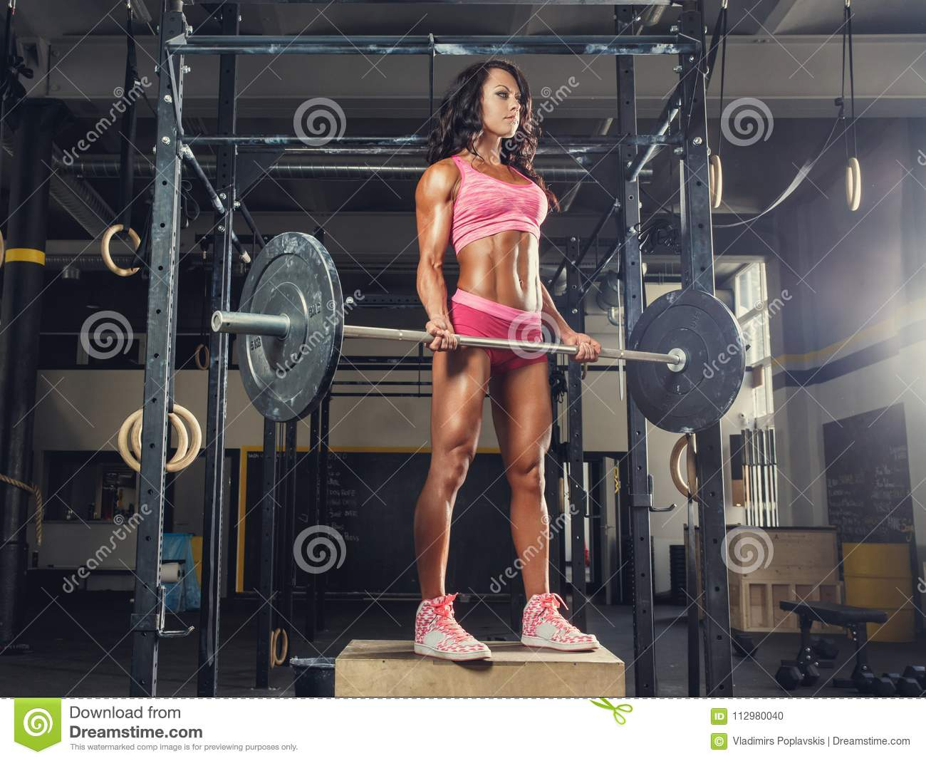 Female fitness model in a pink sportswear holding barbell in a gym club.