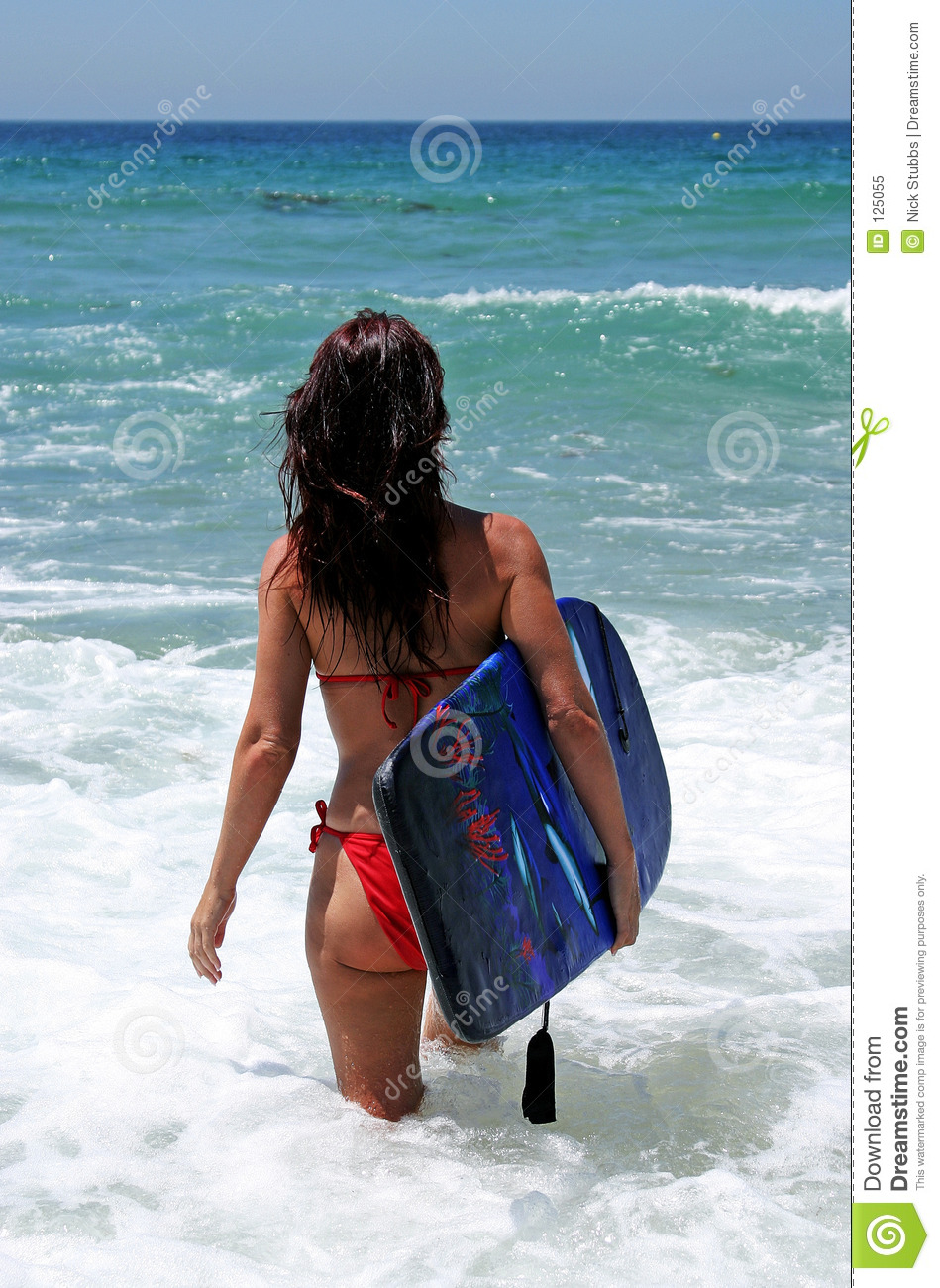 attractive young woman in red bikini walking out to blue sea on sunny beach with body board und