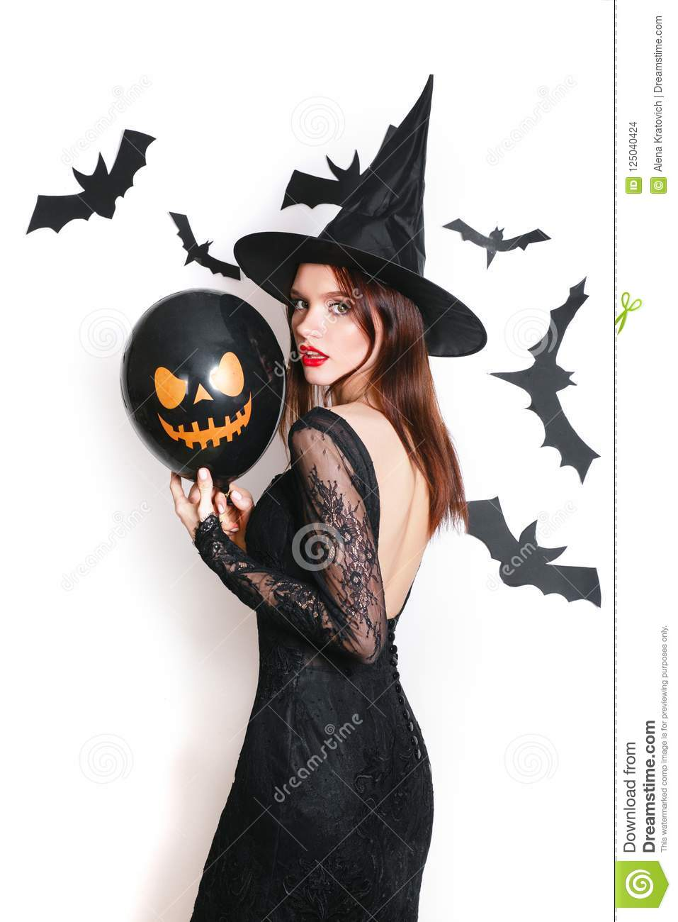 Delightful Beautiful Woman In Black Witch Halloween Costumes With Balloon On Party  Over White Background
