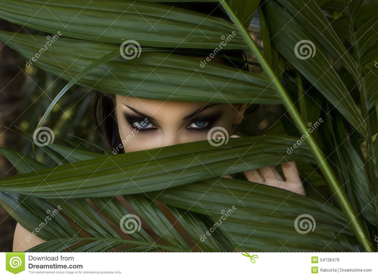 beautiful woman hiding behind the palm leaves. Beautiful st