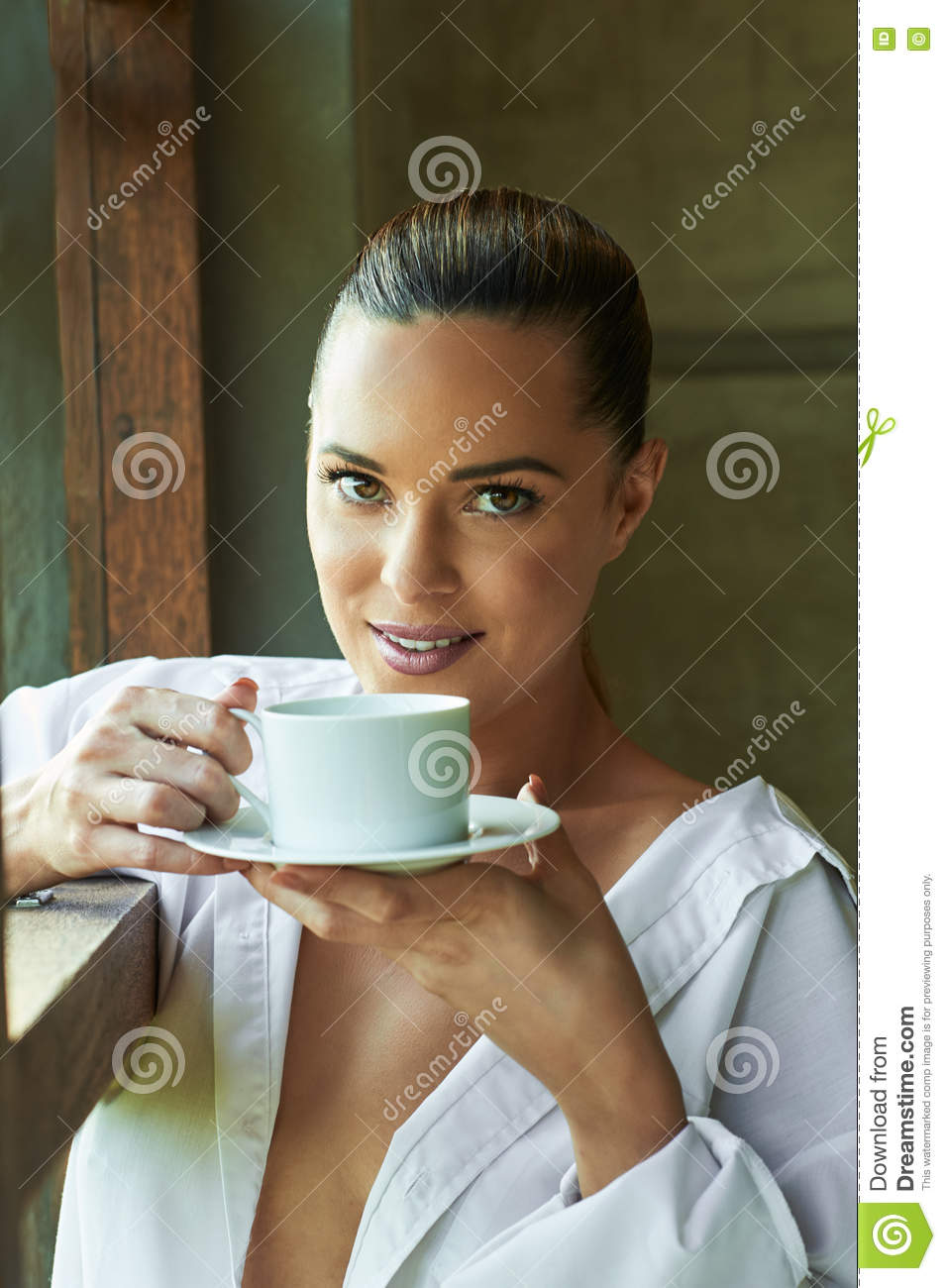 Beautiful Woman Looking Out A Window With Tea Or Coffee Pon