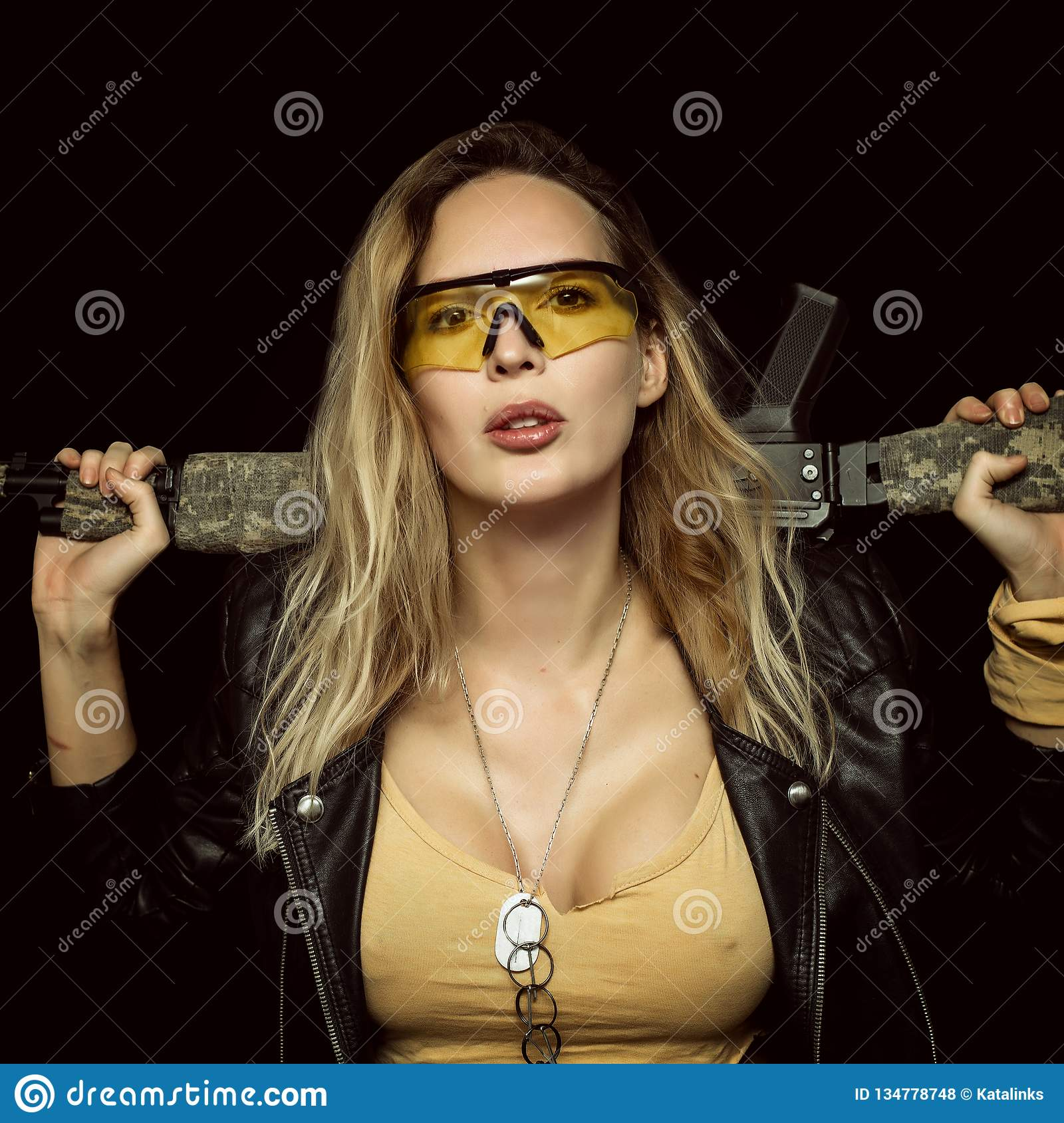 blond dangerous woman with automatic rifle