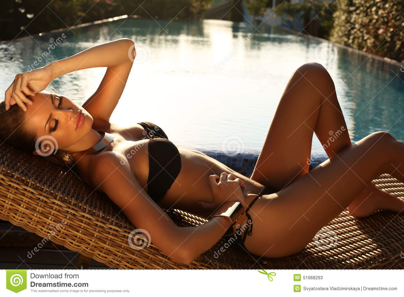 blond girl in black bikini relaxing beside a swimming pool
