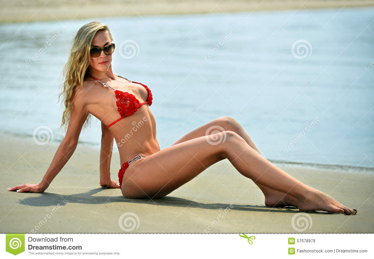 Blonde Bikini Model Laying On The Ocean Beach