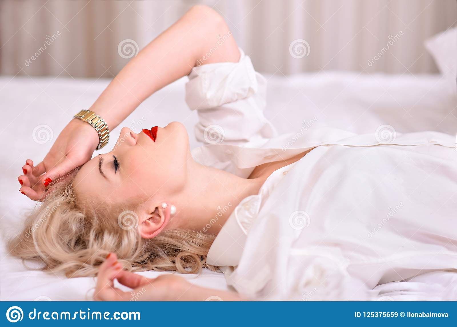 blonde with red lipstick ,in white male shirt, lies on white bed in profile  with eyes closed