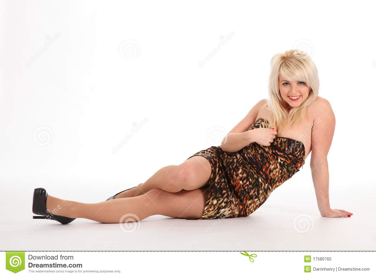 cd433aef6d2 Cheerful, young blonde woman, sitting on the floor. Girl wearing short  patterned dress and high heels. Full body shot on white back drop.