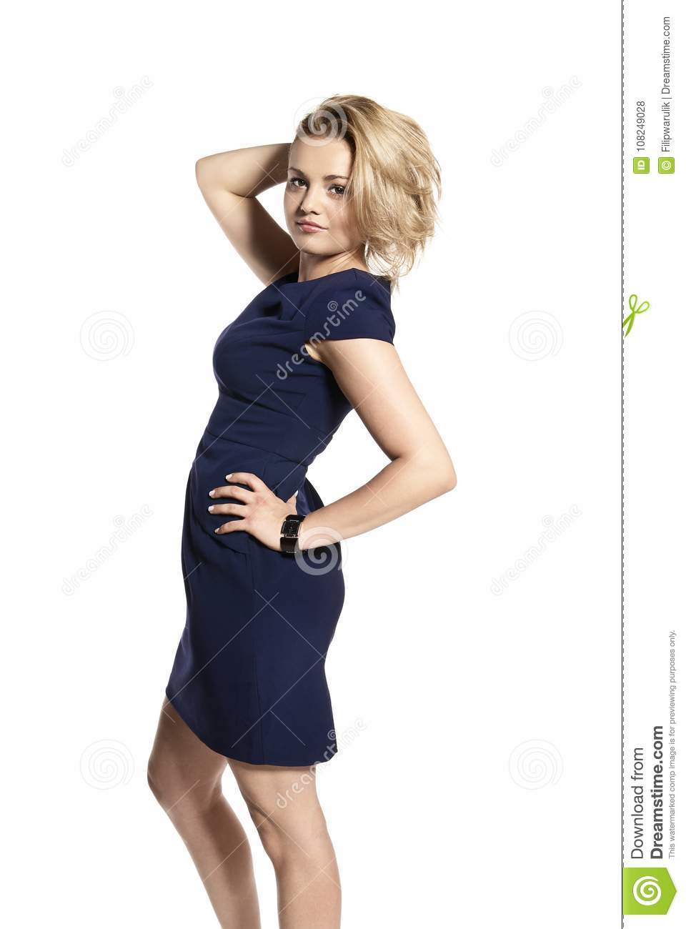 73f72f1ce blonde young woman in a navy blue dress poses in front of the camera.  Isolated on white background.