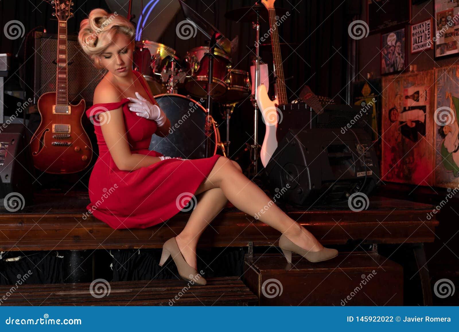 Sexy blondezitting op een stadium voor muzikale instrumenten