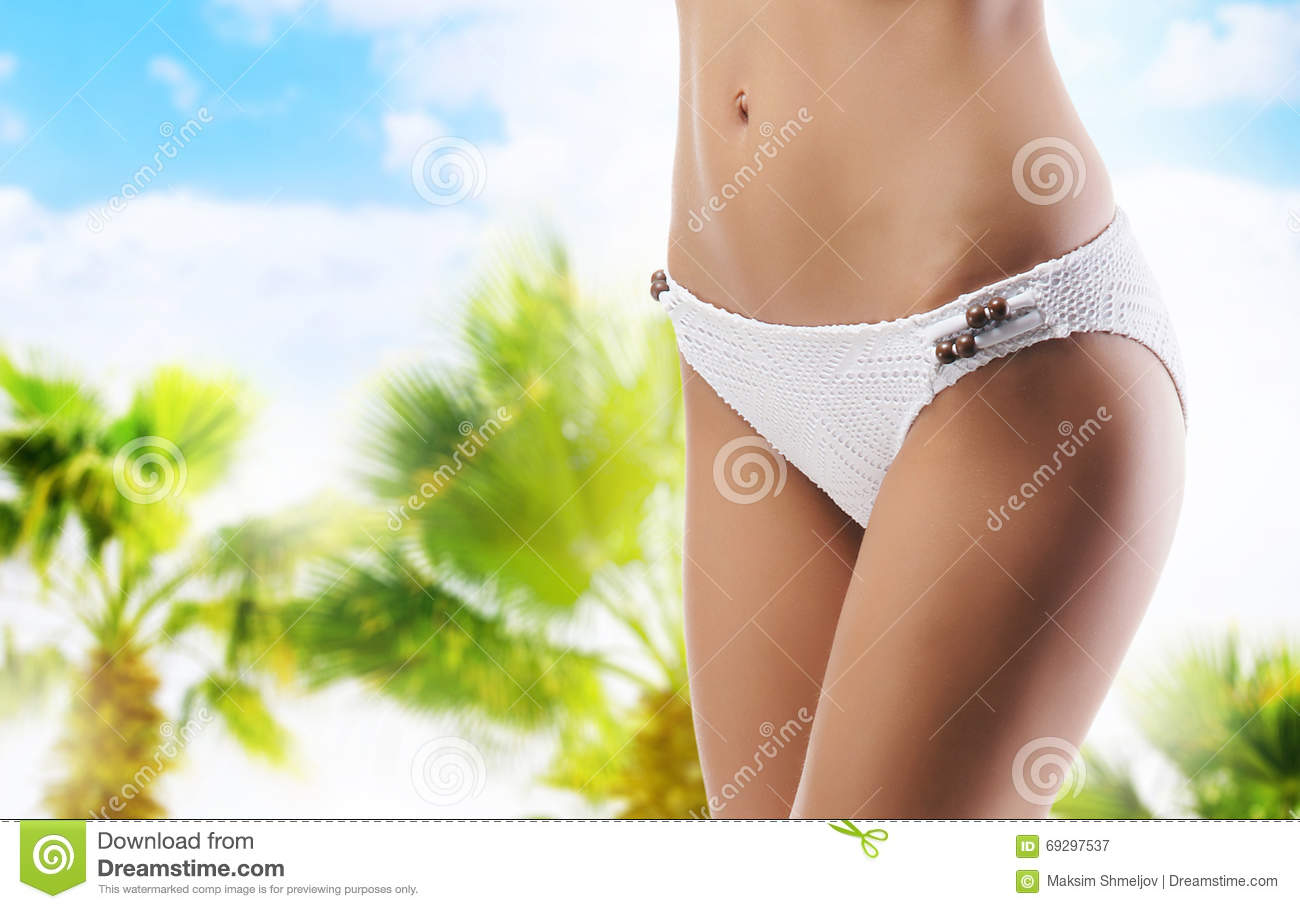e87531f182 Closeup of and sporty female body. Girl with a perfect body shape resting on  a summer vcation. Sea