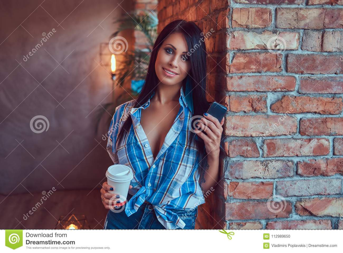 A happy brunette in a flannel shirt and jeans holds a cup of coffee and the phone posing against a brick wall.