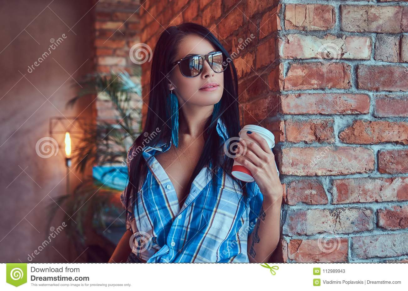 A happy brunette in flannel shirt and sunglasses holds a cup of coffee posing against a brick wall.