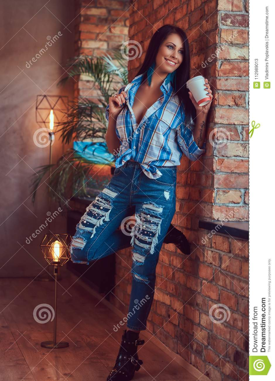 A brunette in a flannel shirt and jeans holds a cup of coffee posing against a brick wall.