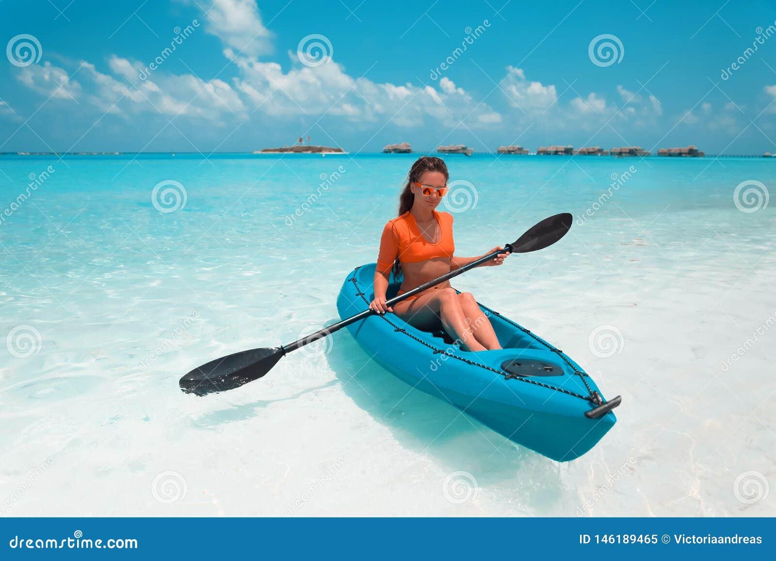 Brunette Paddling A Kayak  Woman Exploring Calm Tropical Bay
