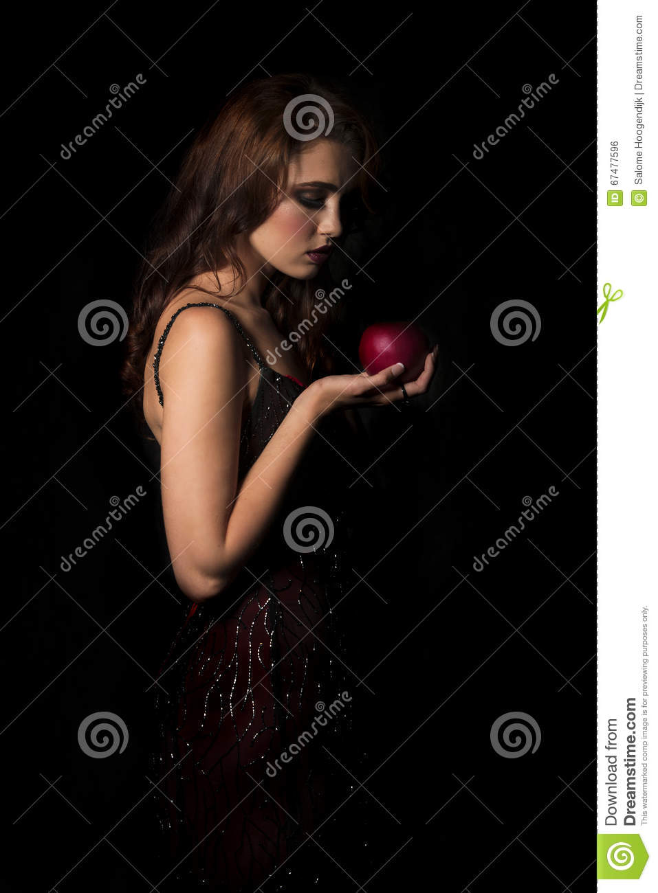 brunette woman with dark red dress looking down at red apple in her hand