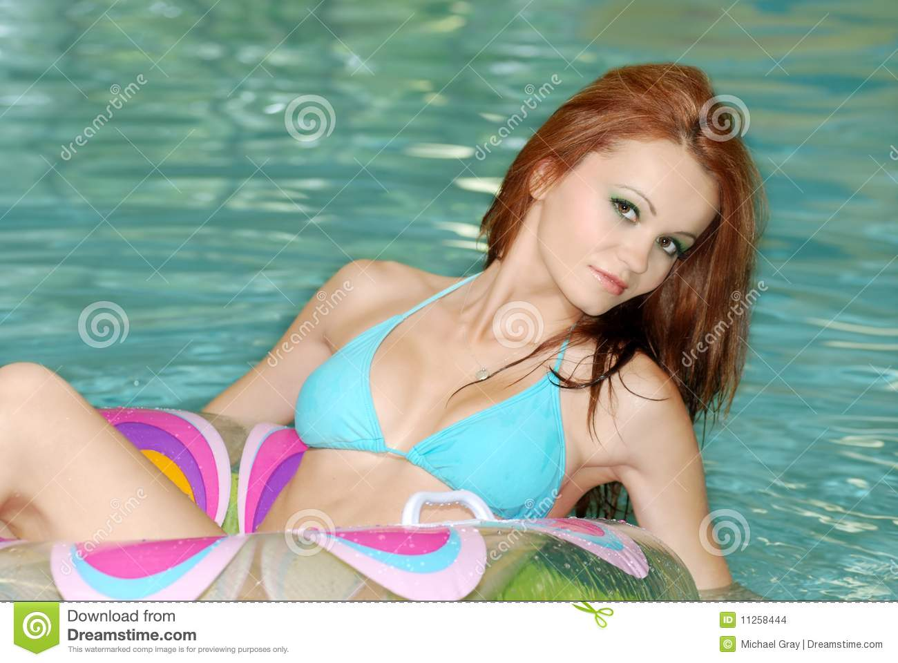 Sexy Brunette Woman Floating In Swimming Pool Stock Images