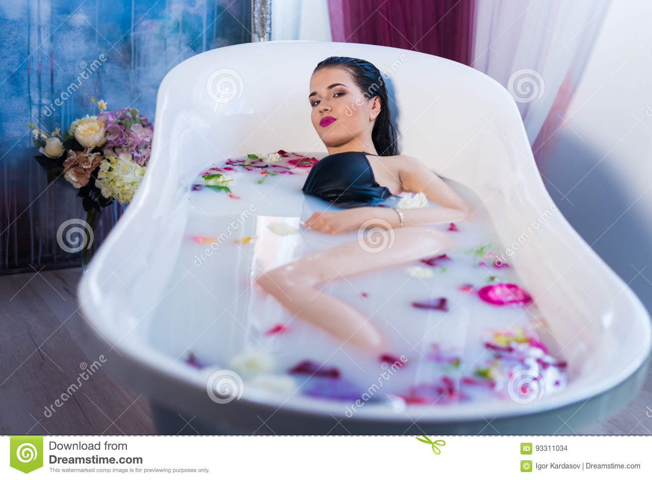 Brunette Woman Relaxing In Hot Milk Bath With Flowers Stock Photo ...