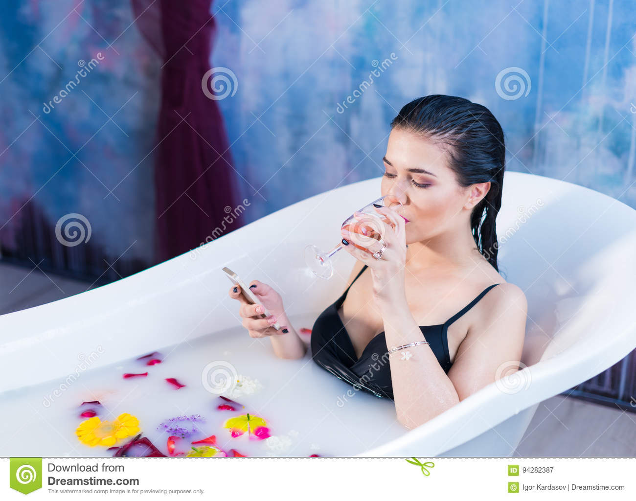 Brunette Woman Is Sitting In Bath And Chatting On Smartphone Stock ...