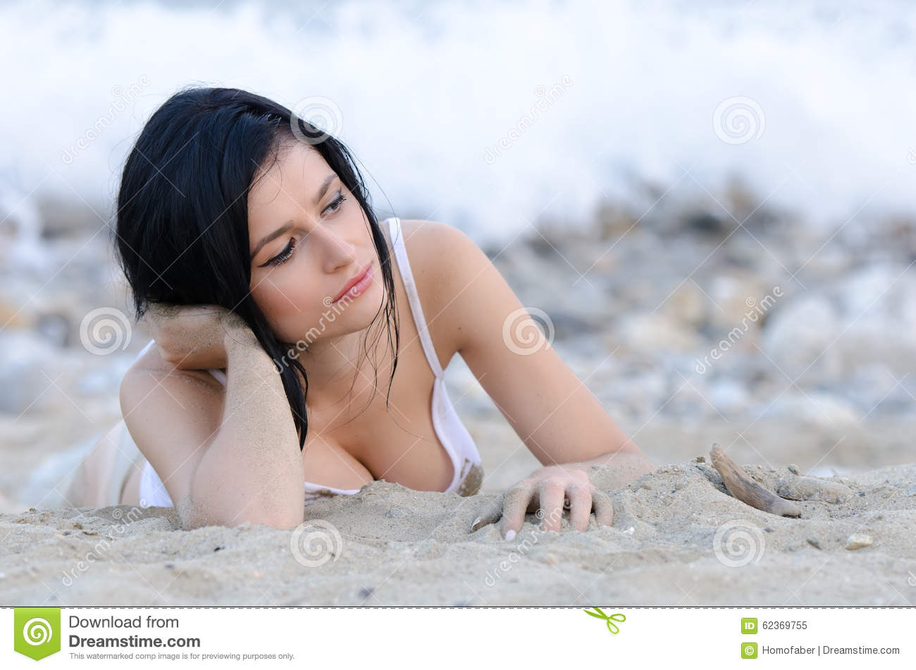brunette woman, wear wet t-shirt as she lie on sandy beach stock