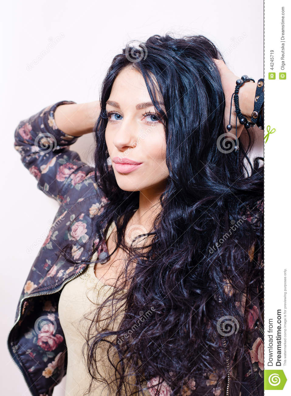 brunette young pretty lady with long hair in flower printed leather jacket having fun sensually looking at camera