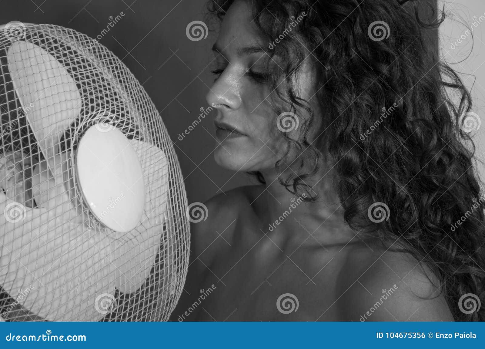 Sexy Brunettemädchen mit dem gelockten Haar mit Ventilator