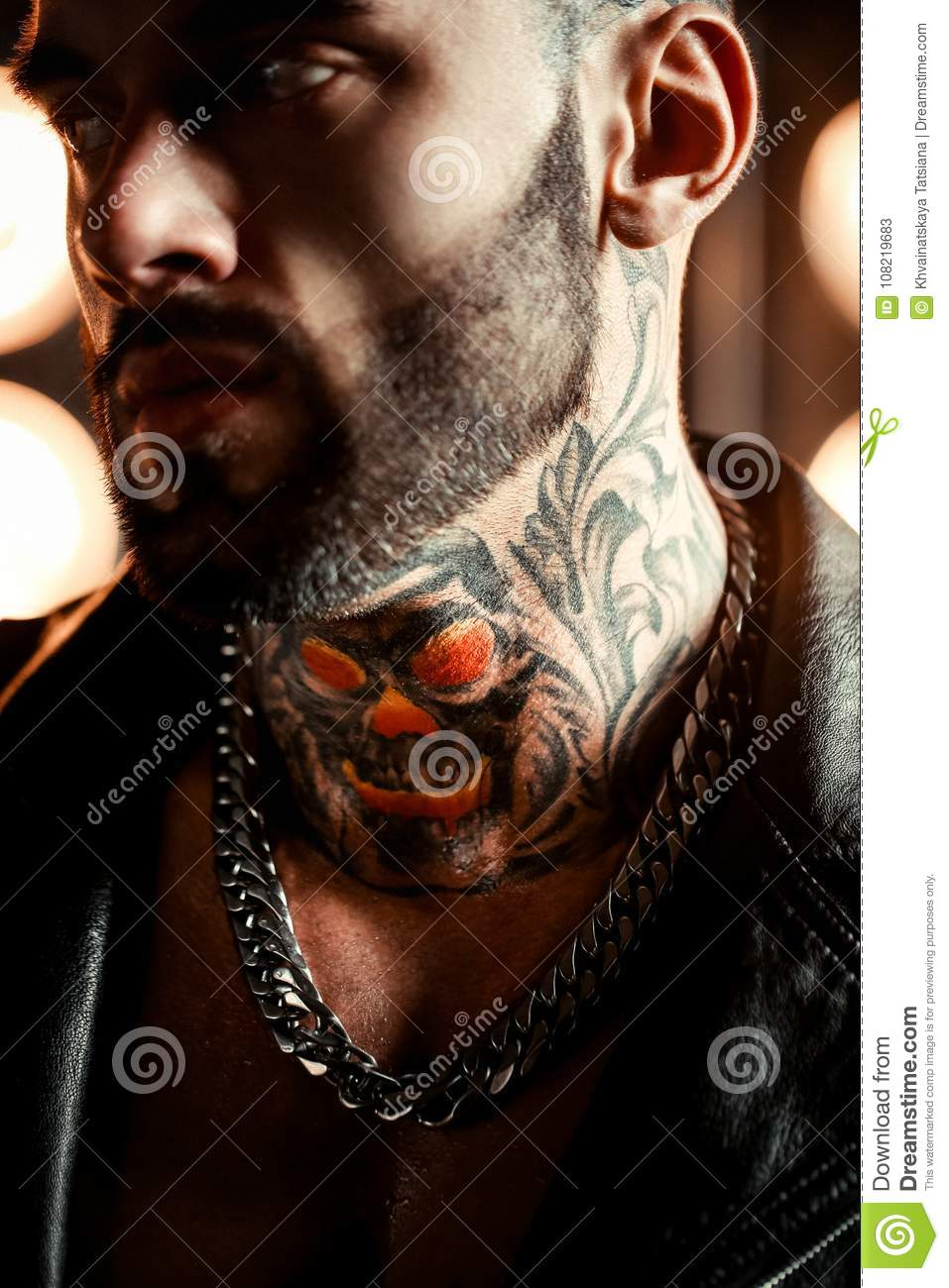 closeup portrait of brutal handsome male model in fashion leather jacket and with a black beard. Tattoo skull and