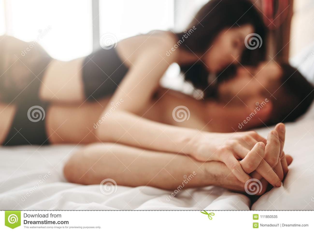 Couple Lying And Kissing On Big White Bed Stock Image ...