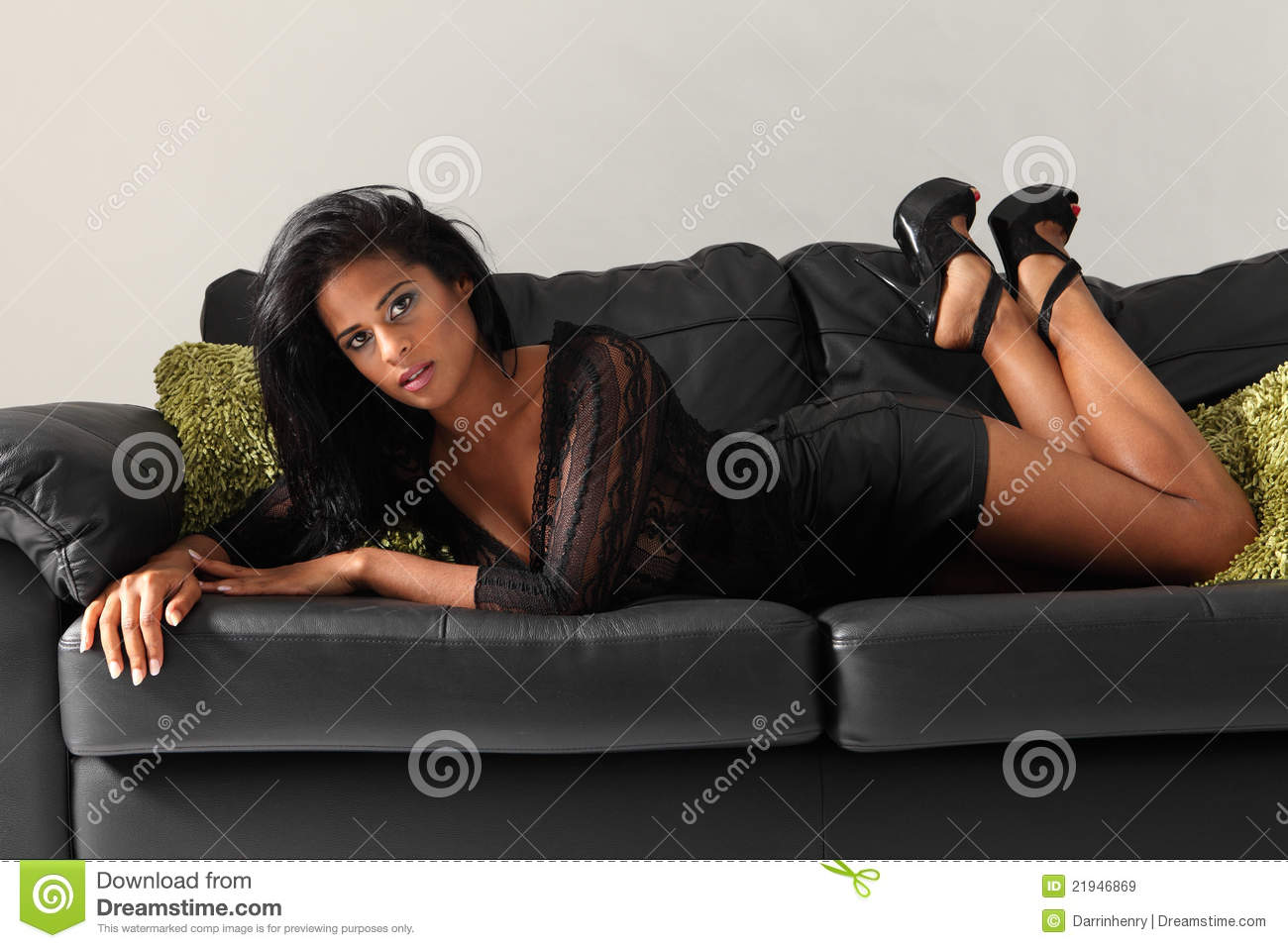 curvy african american girl on leather sofa stock image