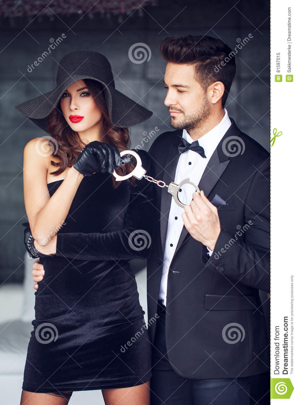 dominatrix woman holding on handcuffs young macho lover in