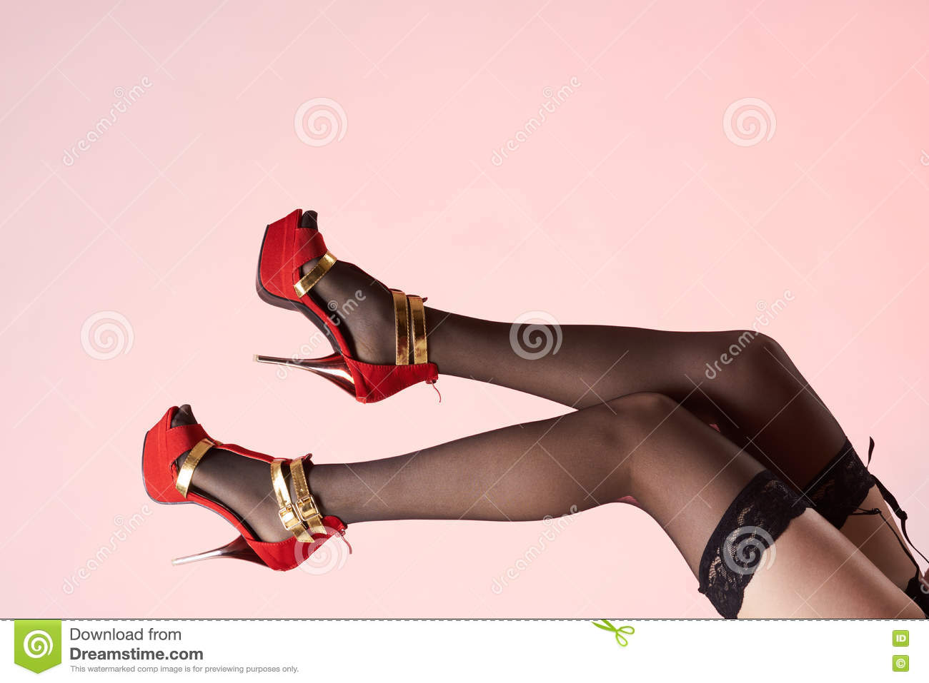 0a1b94251 female legs wearing red shoes high golden heels and platform in black nylon  stockings.