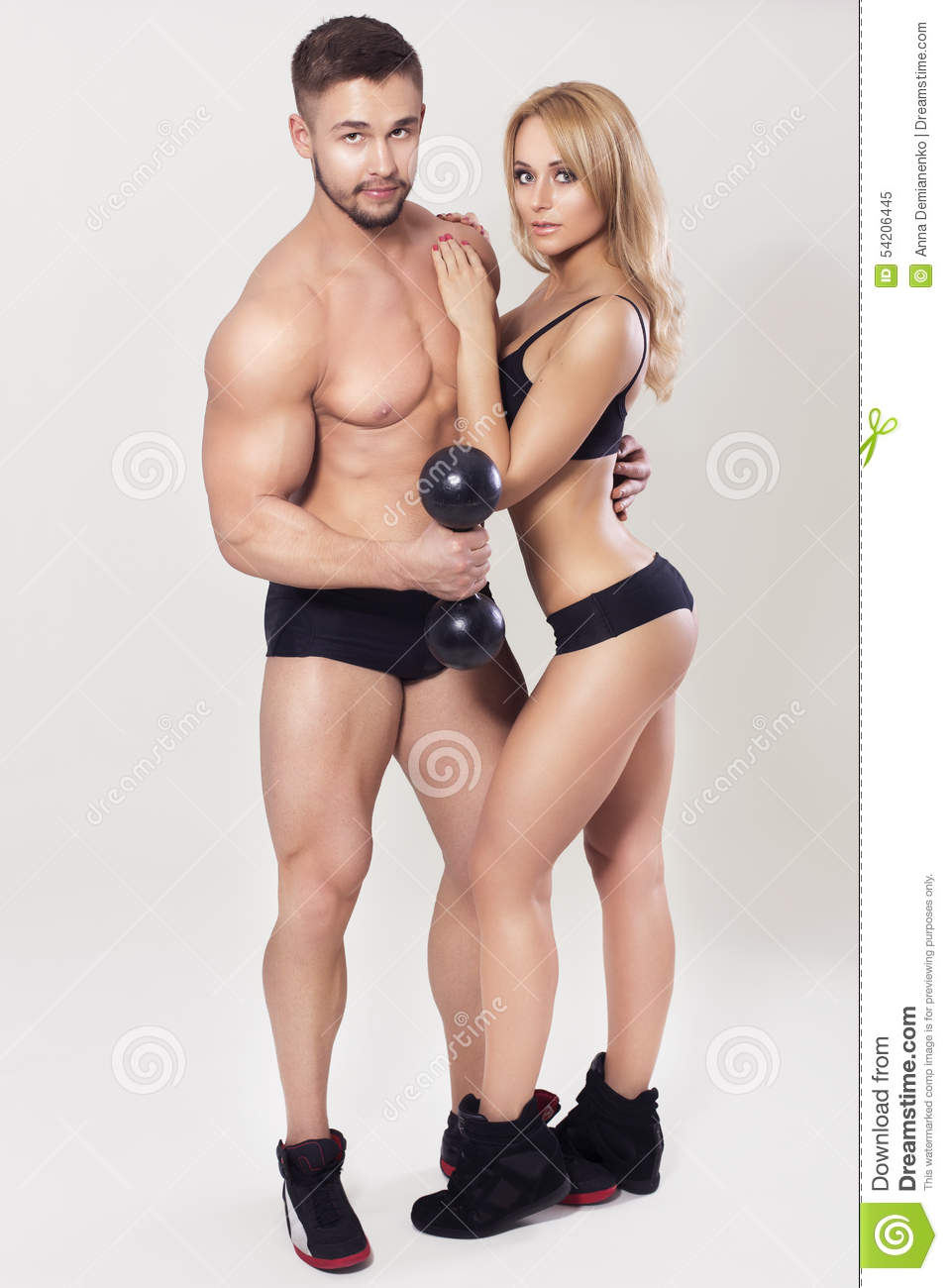 fit muscled couple in sportswear on neutral grey background
