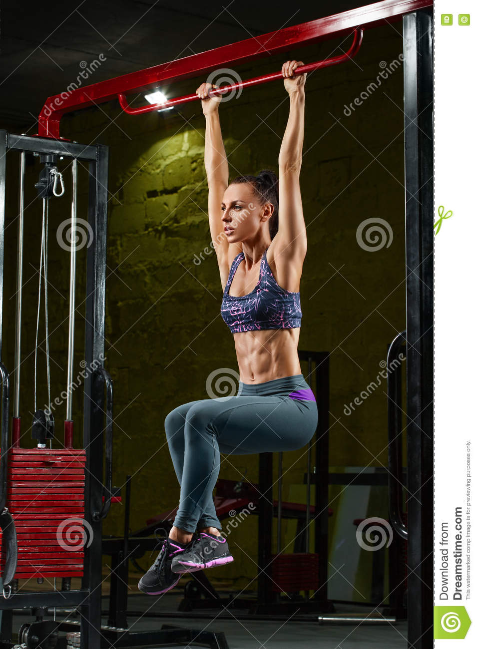 fitness girl doing pulls up on horizontal bar in gym. Muscular woman, abs, shaped abdominal