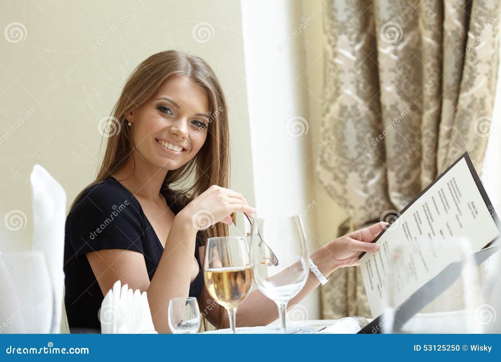 Sexy Frau, die mit Menü an der Mittagspause aufwirft