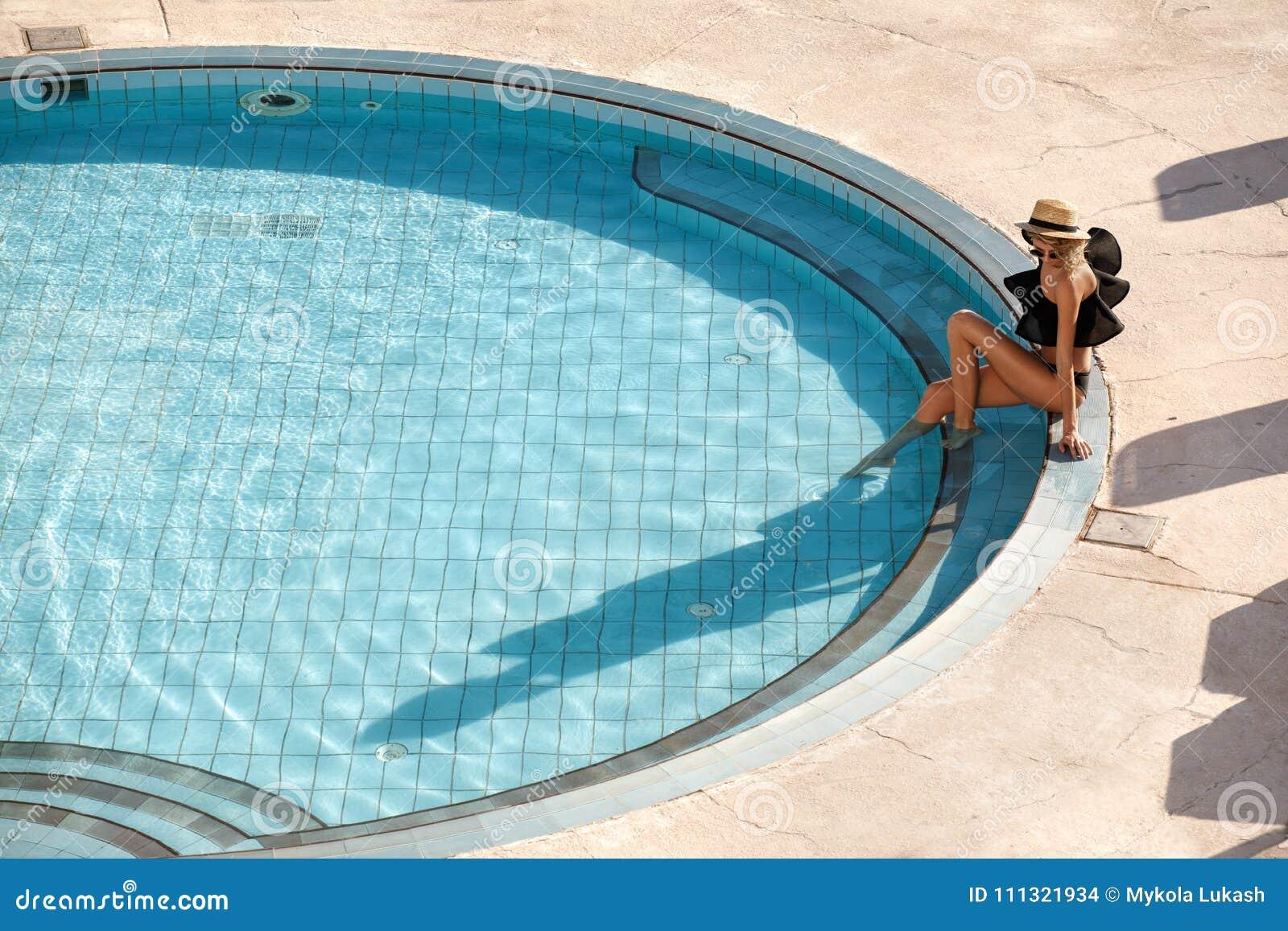 Sexy Frau im Bikini Sommersonne genießend und während der Ferien nahe dem Pool bräunend