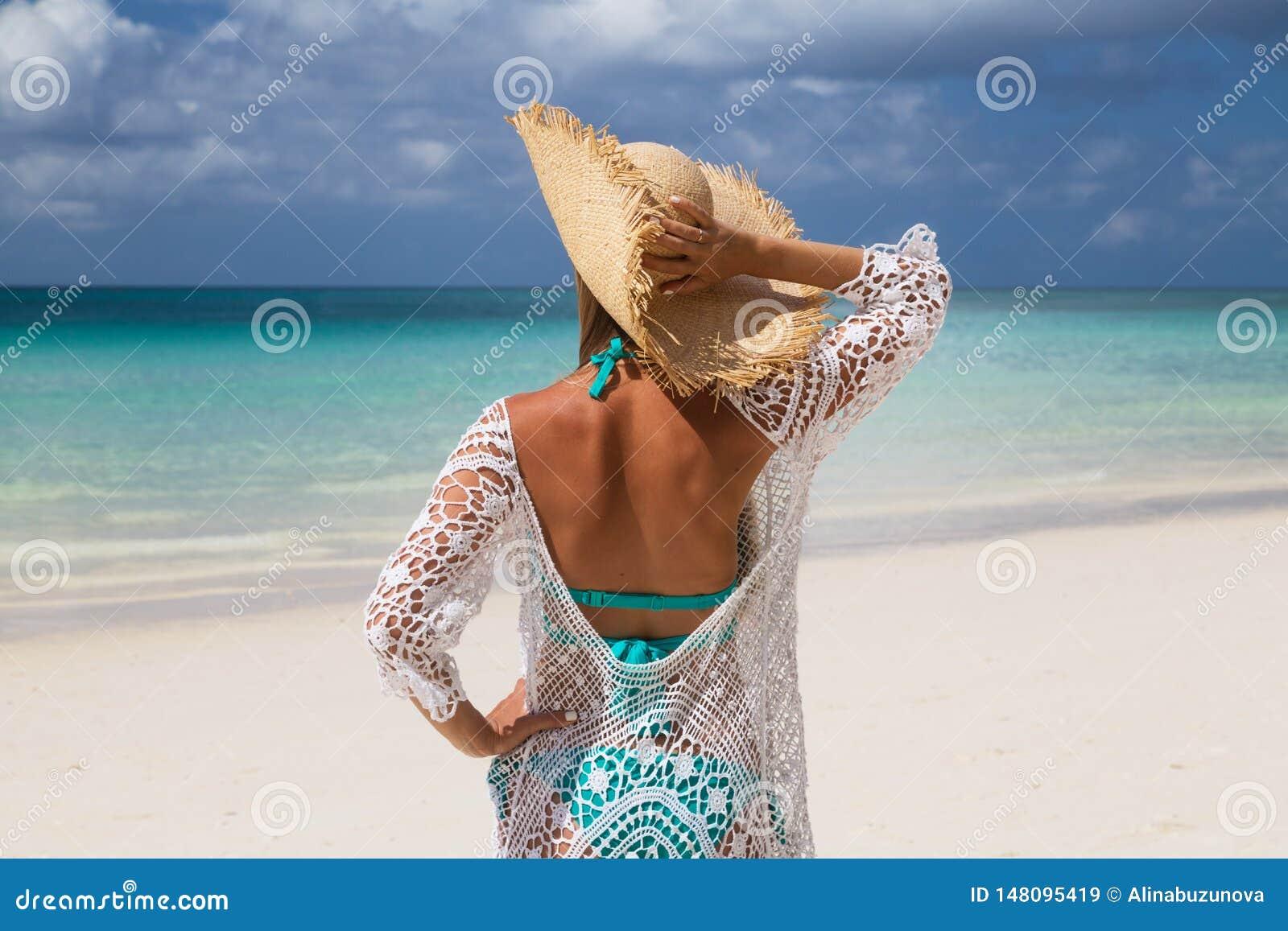 Sexy gelooid meisje in blauwe bikini, strohoed die van zich erachter op de kust bevinden Het mooie model zonnebaadt en rust op ov