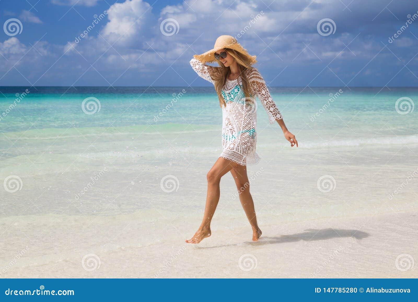 Sexy gelooid meisje die in blauwe bikini en witte tunica op de kust lopen Het mooie model zonnebaadt en rust op overzees Concept