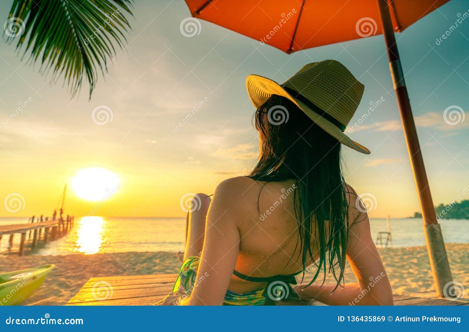 Sexy, geniet en ontspan van de Kaukasische bikini van de vrouwenslijtage liggend en het zonnebaden sunbed onder bij zandstrand bi