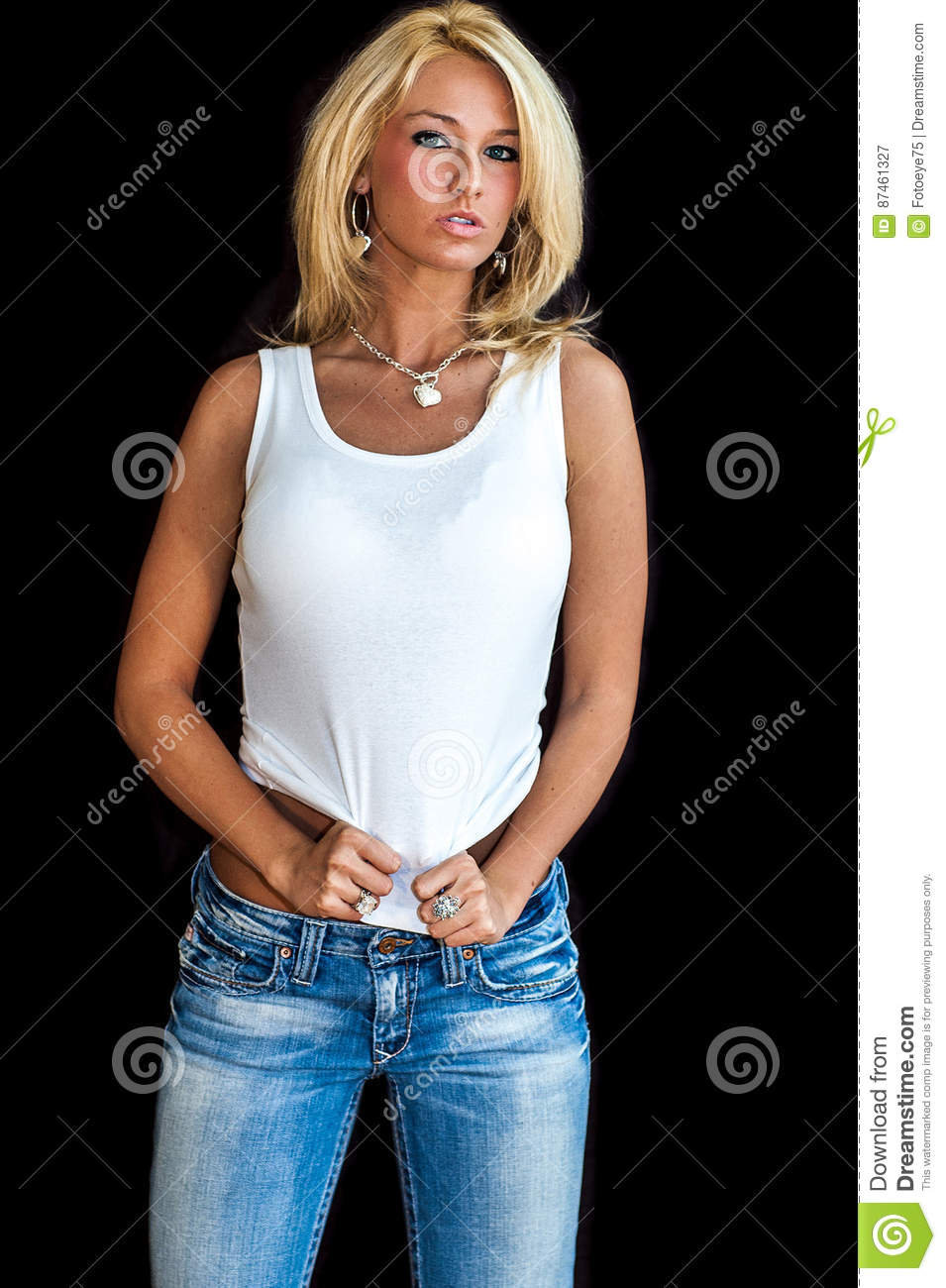 39604bf756a5 woman / girl blonde fashion model. Dressed in denium blue jeans and white  tank top shirt. Woman / female studio portrait isolated against black  background.
