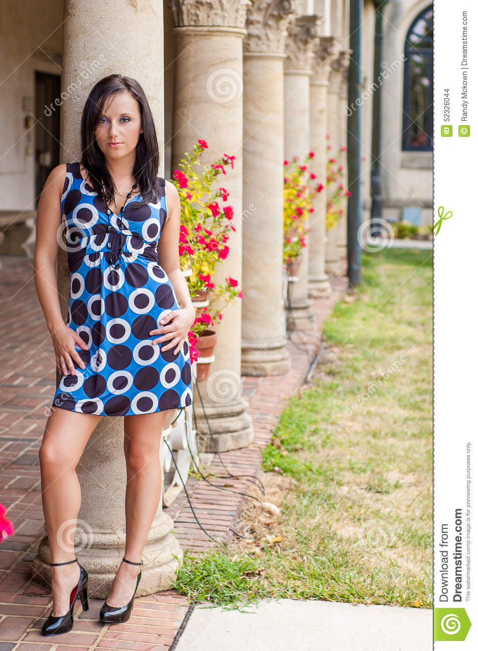 b7b0d57d55c girl   woman   female with dark brown brunette hair. Wearing a pokadot blue  dress that shows soft skin smooth legs. Standing against elegant pillars.
