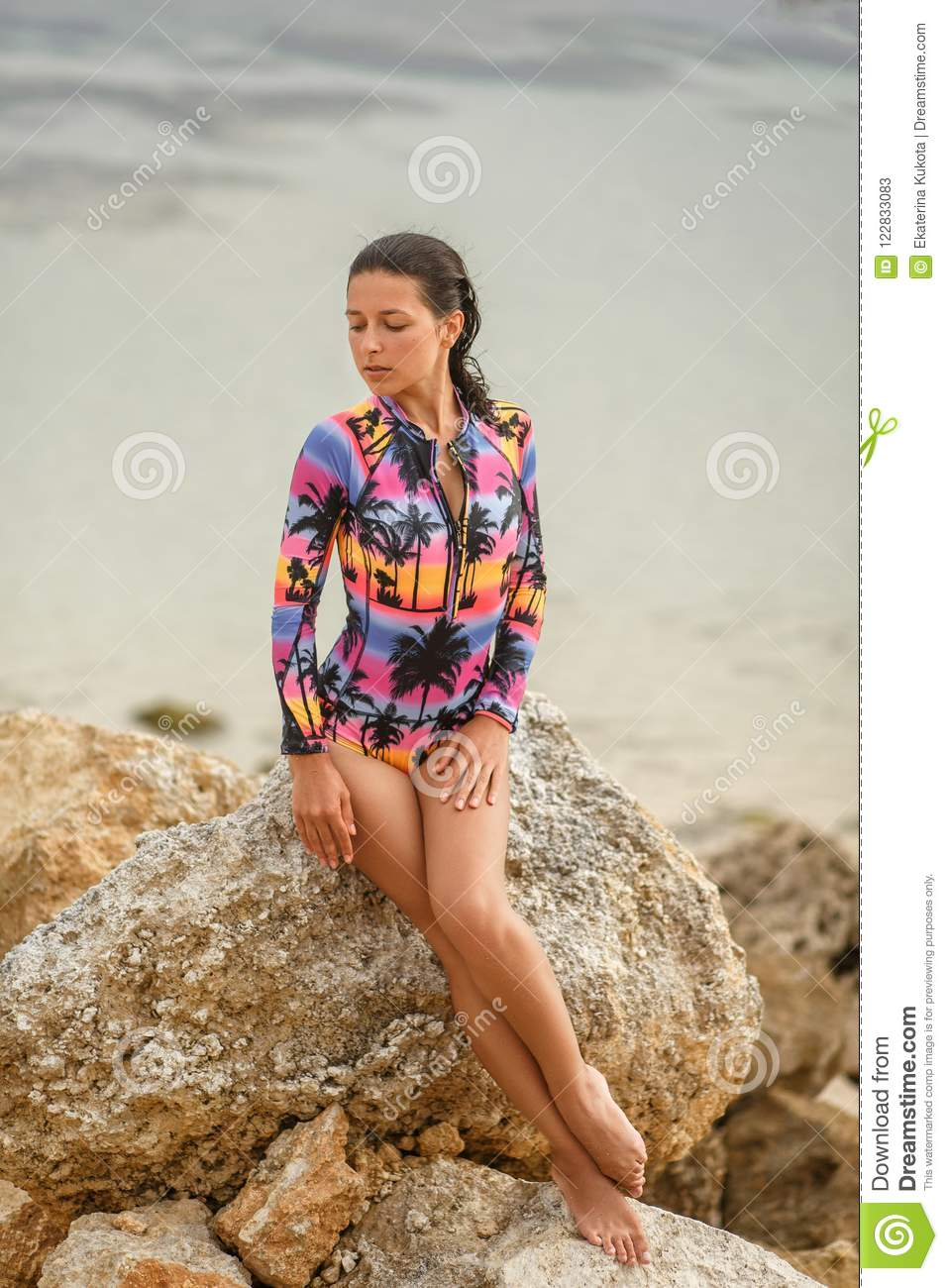 girl posing sitting on rocks at the beach
