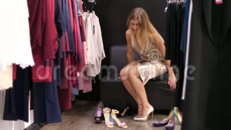 70e660df005 A girl, a tall, long-legged, beautiful blond woman trying on gold-colored  shoes on a high heeled heel in a stylish.