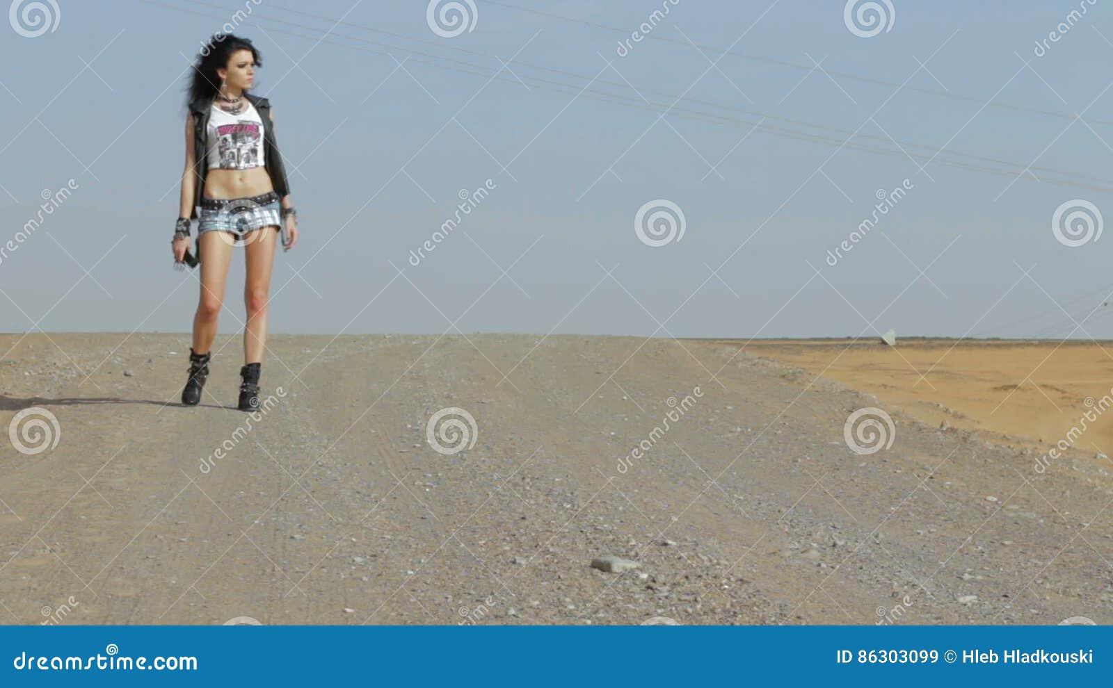 Girl walking on the desert road. HD stock video footage