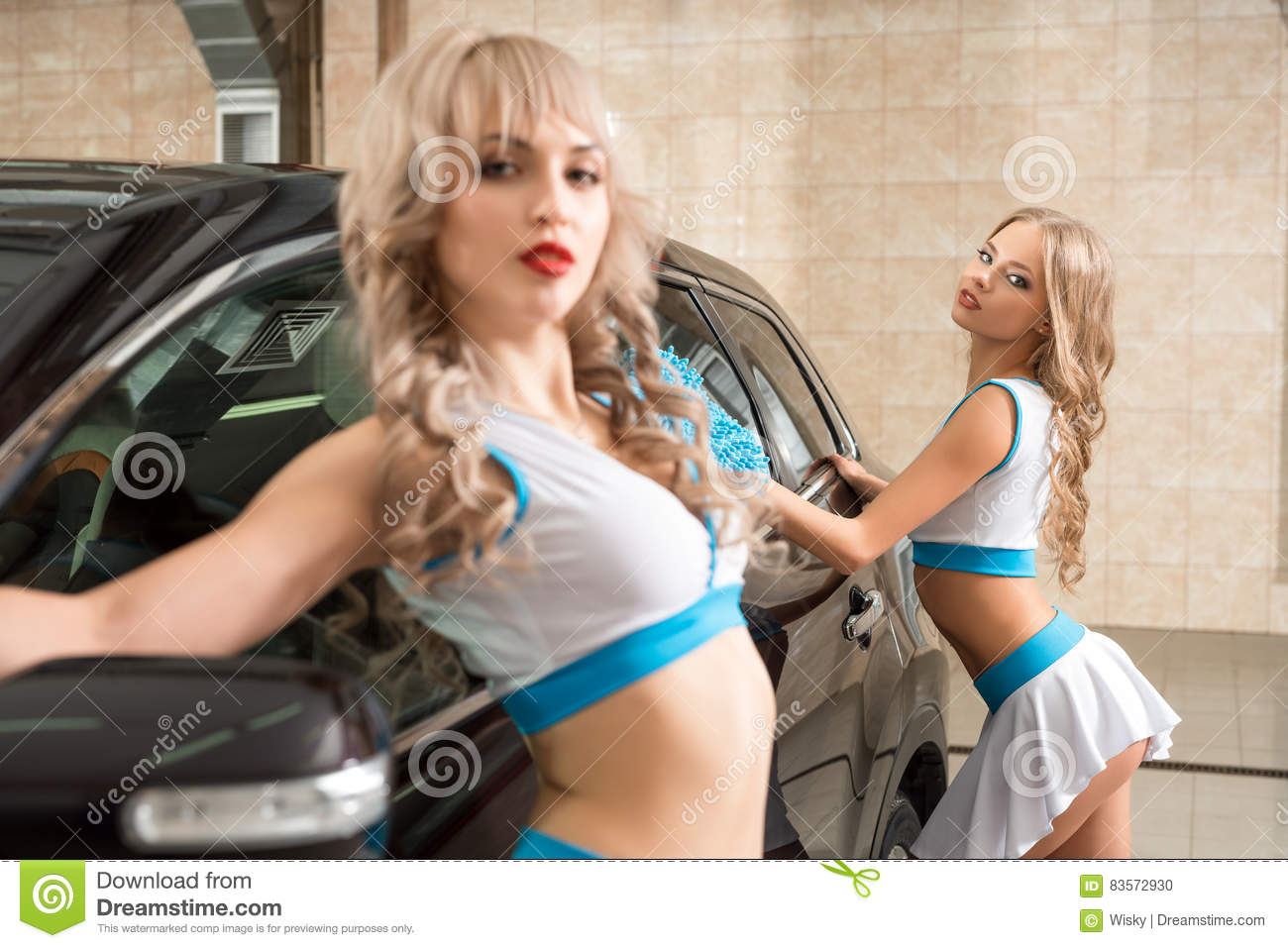 girls in formula one style posing at carwash