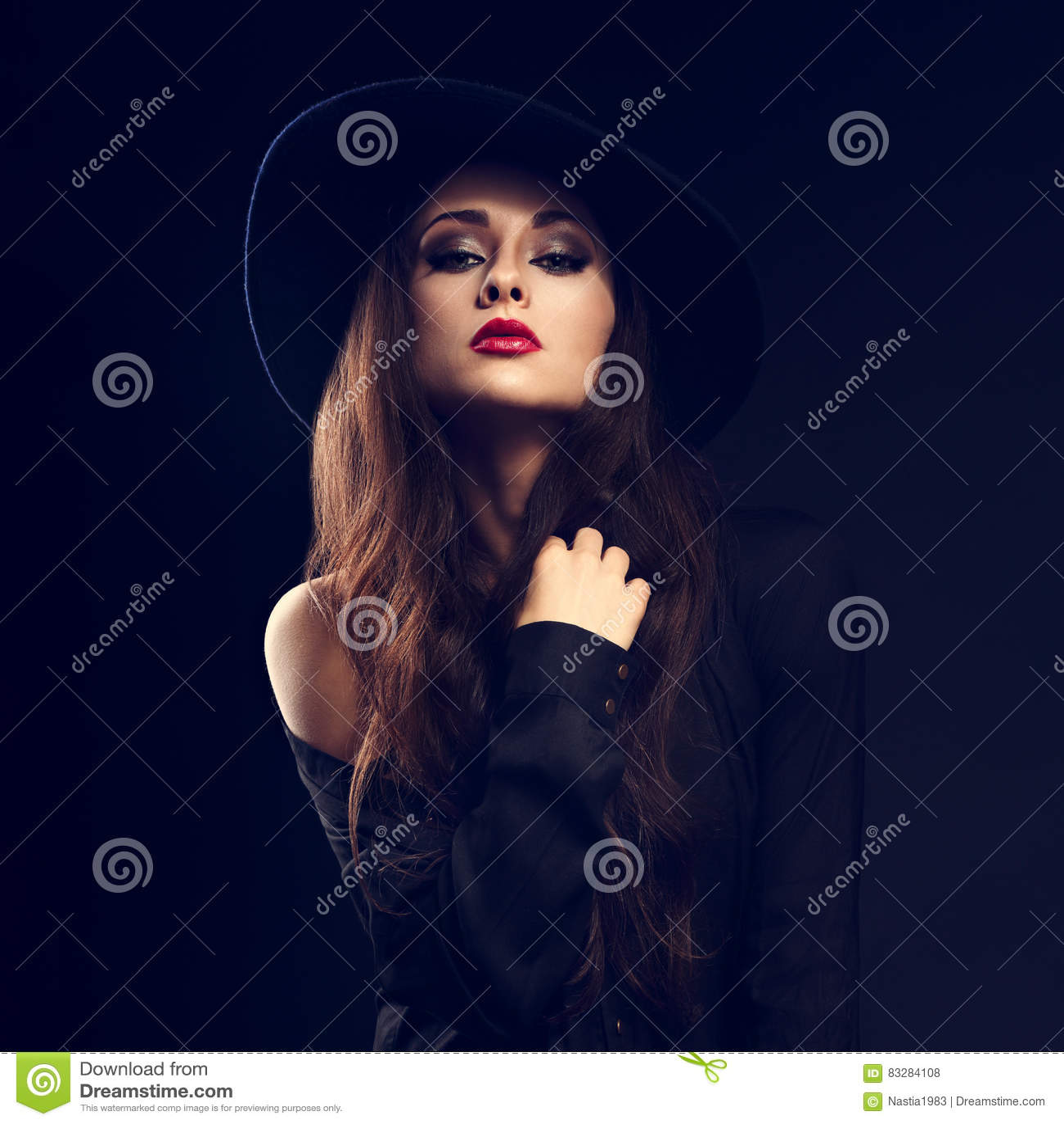 glamour female model posing in black shirt and elegant hat