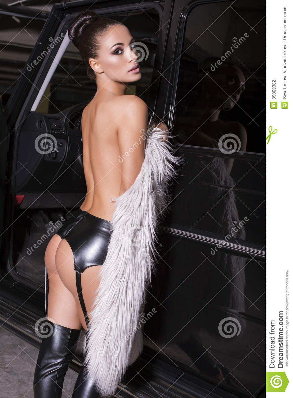 sexy glamour woman with naked back with fur coat posing beside a car