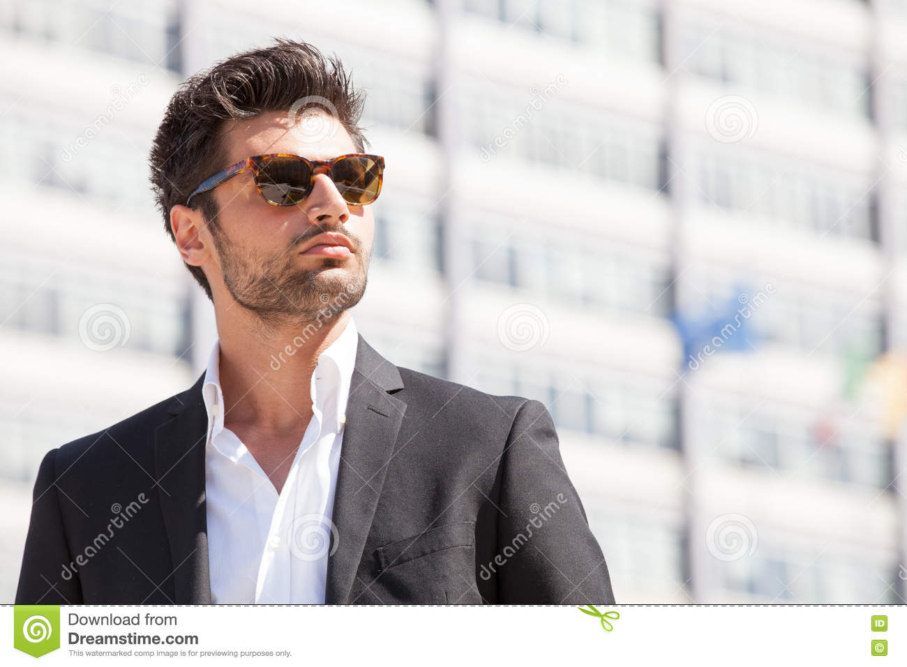 688068b3ca5 A beautiful and charming man with sunglasses outdoors. Stubble and blacks  hair. Intense light. White shirt and stylish jacket.
