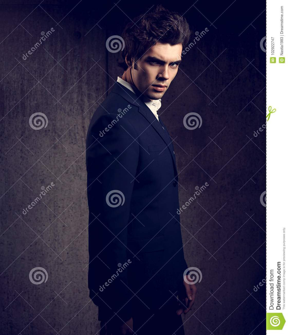40fe3bbd handsome male model posing in blue fashion suit and white style shirt  looking down on dark shadow background. Toned portrait
