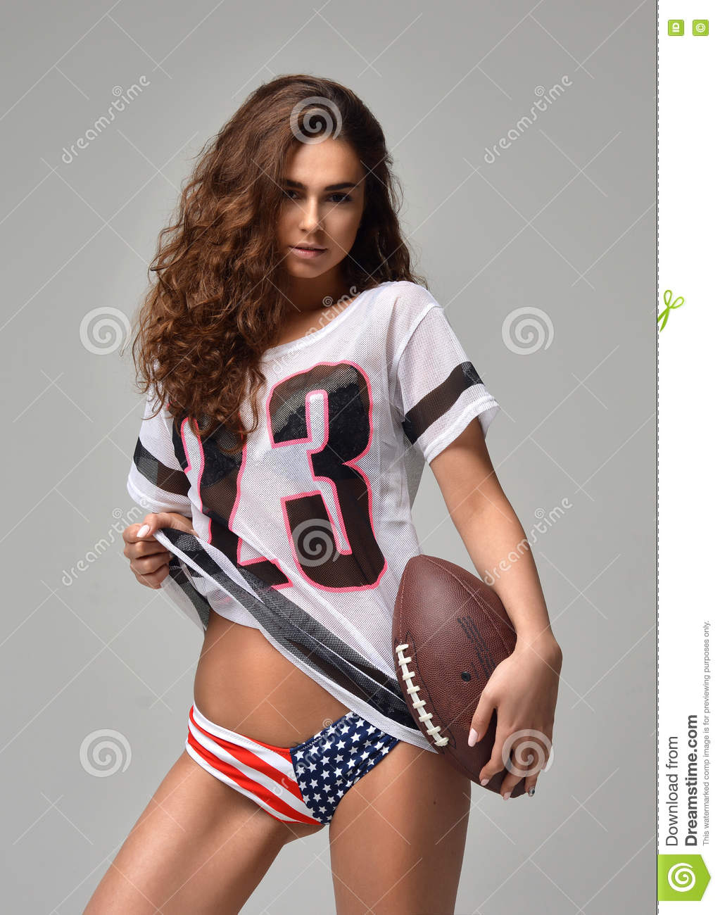 happy Fierce young woman Football Player with ball standing