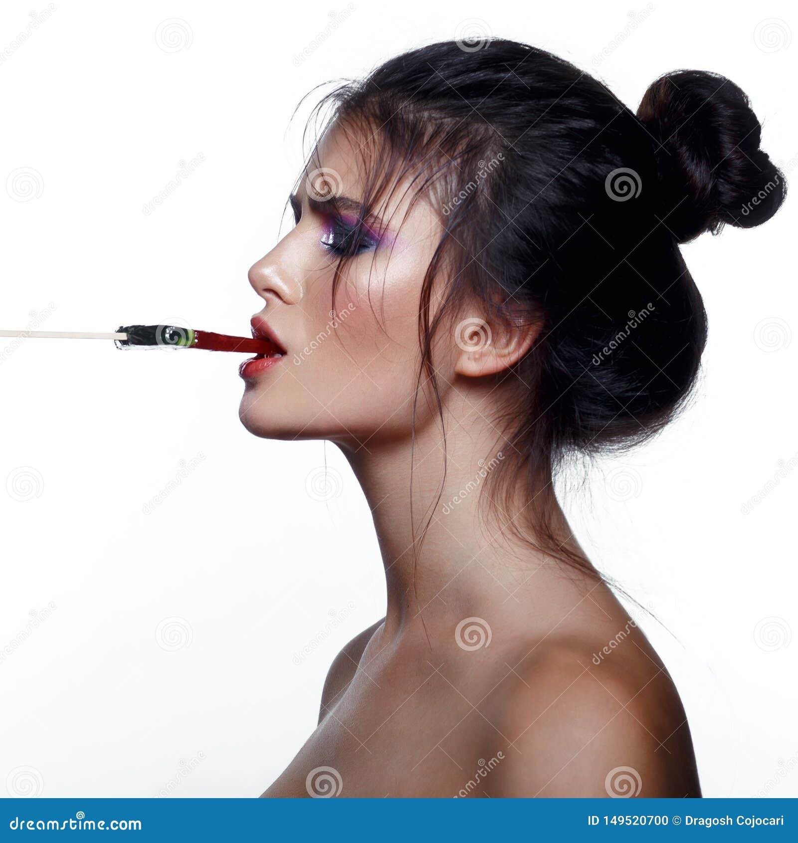 Sexy junge Frau mit den festen Haaren, wenn die nackten Schultern, im Mund halten, einen Lutscher, lokalisiert auf einem wei?en H