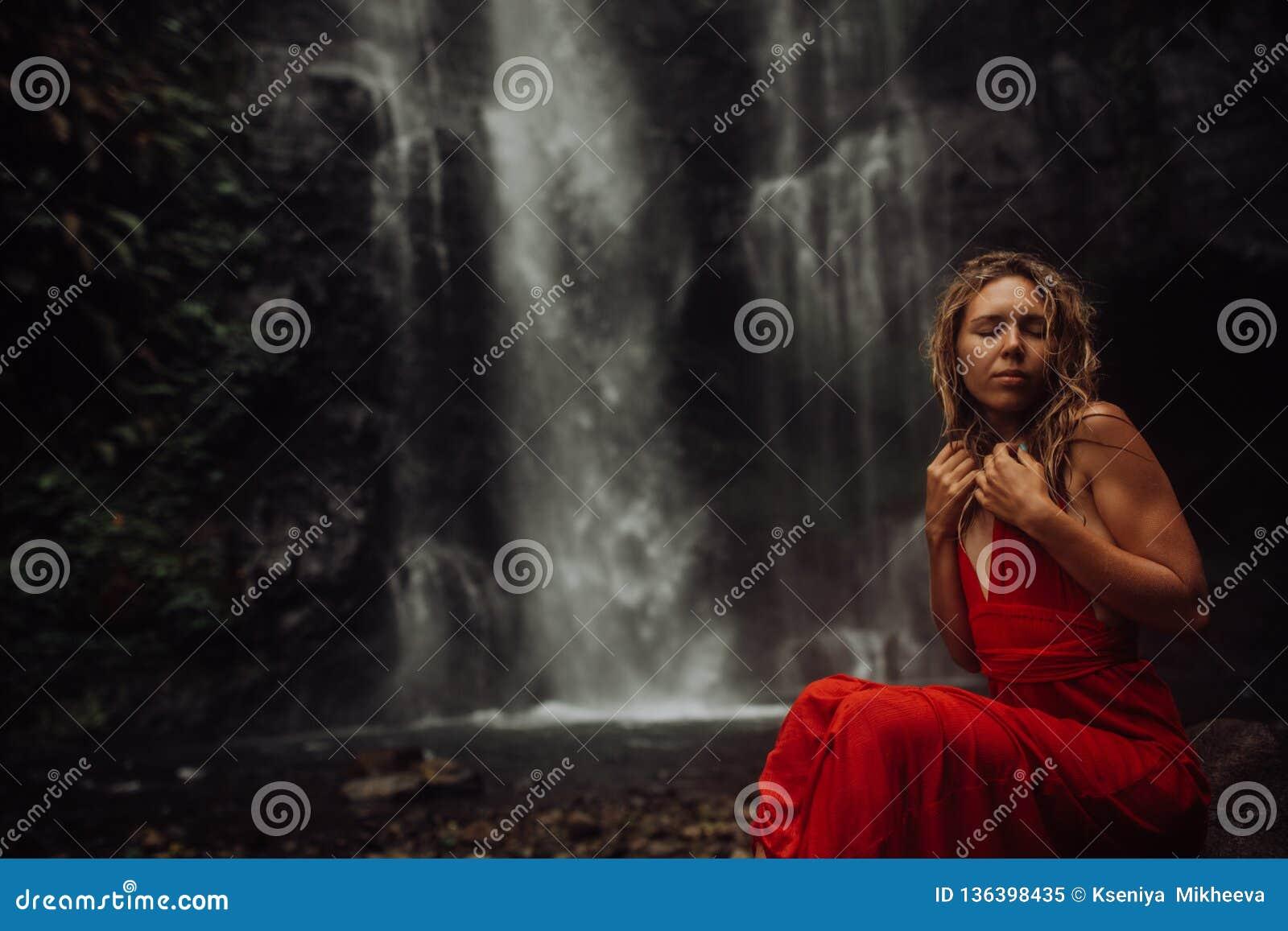 Sexy junges Mädchen im roten Kleid an überraschendem Wasserfall Bali - die beste Kaskade in Indonesien