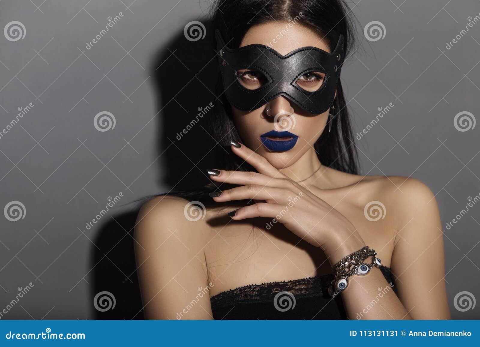 Sexy kaukasische Brunettefrau, die schwarze Spitze, ledernen Katze mas trägt
